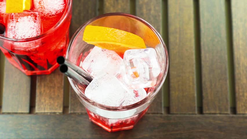 top of view of pouring red spritz aperitif aperol cocktail with orange slices and ice cubes on wood table - HD stock footage clip
