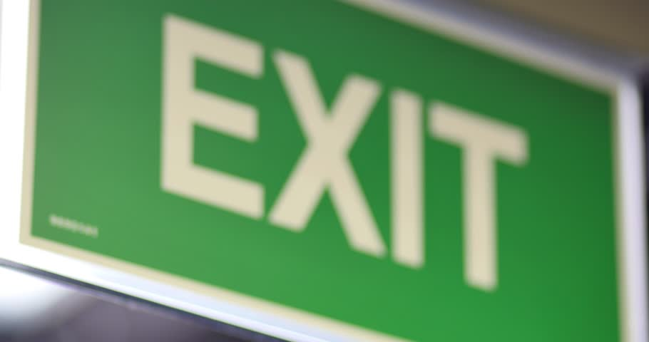 Close up footage of an exit sign, the shot goes out of focus and comes again into focus